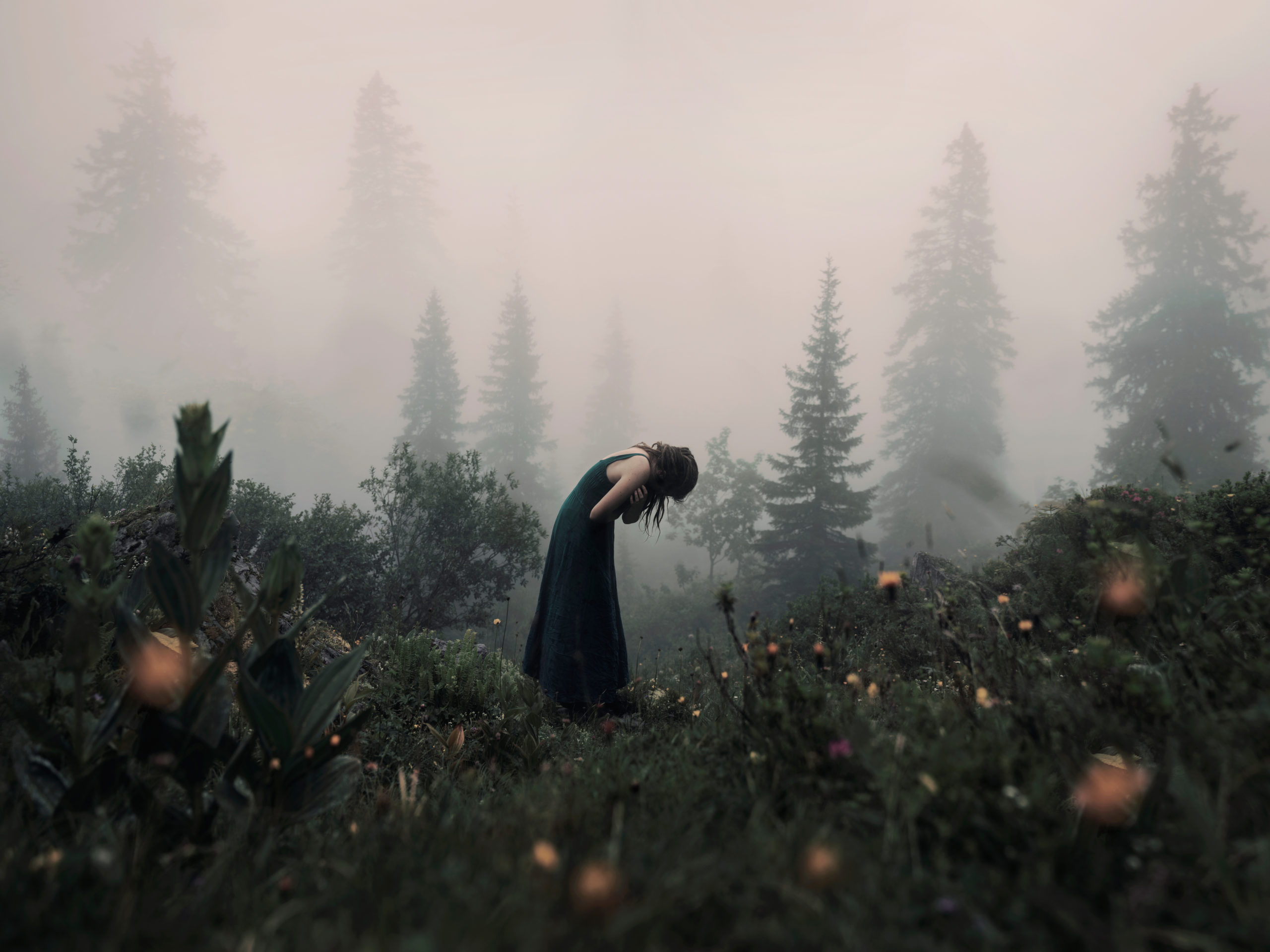 Emotional self portrait showing a woman who appears to be crying in a foggy forest landscape.