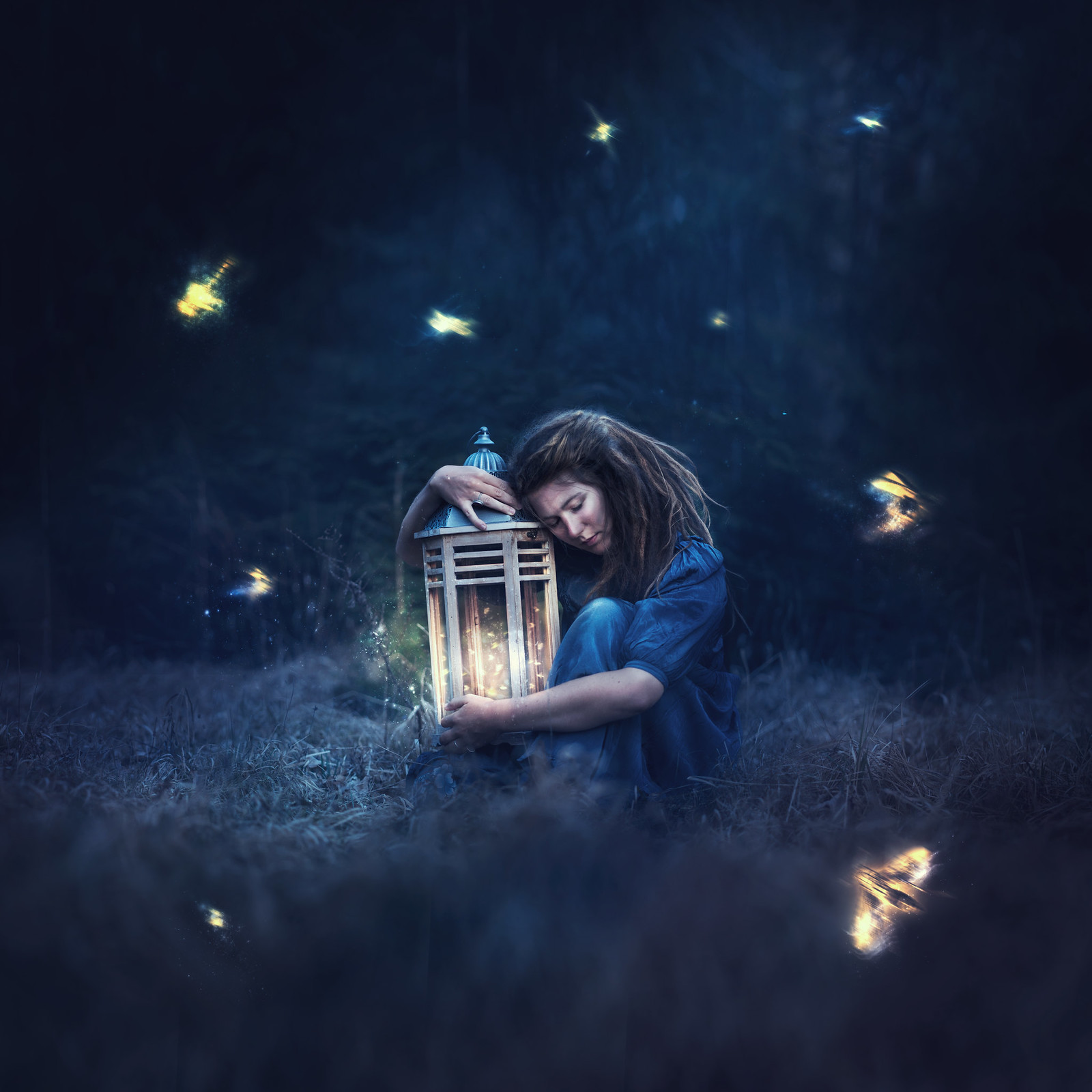 Fantasy self-portrait of a girl holding a lamp in the dark surrounded by fireflies.