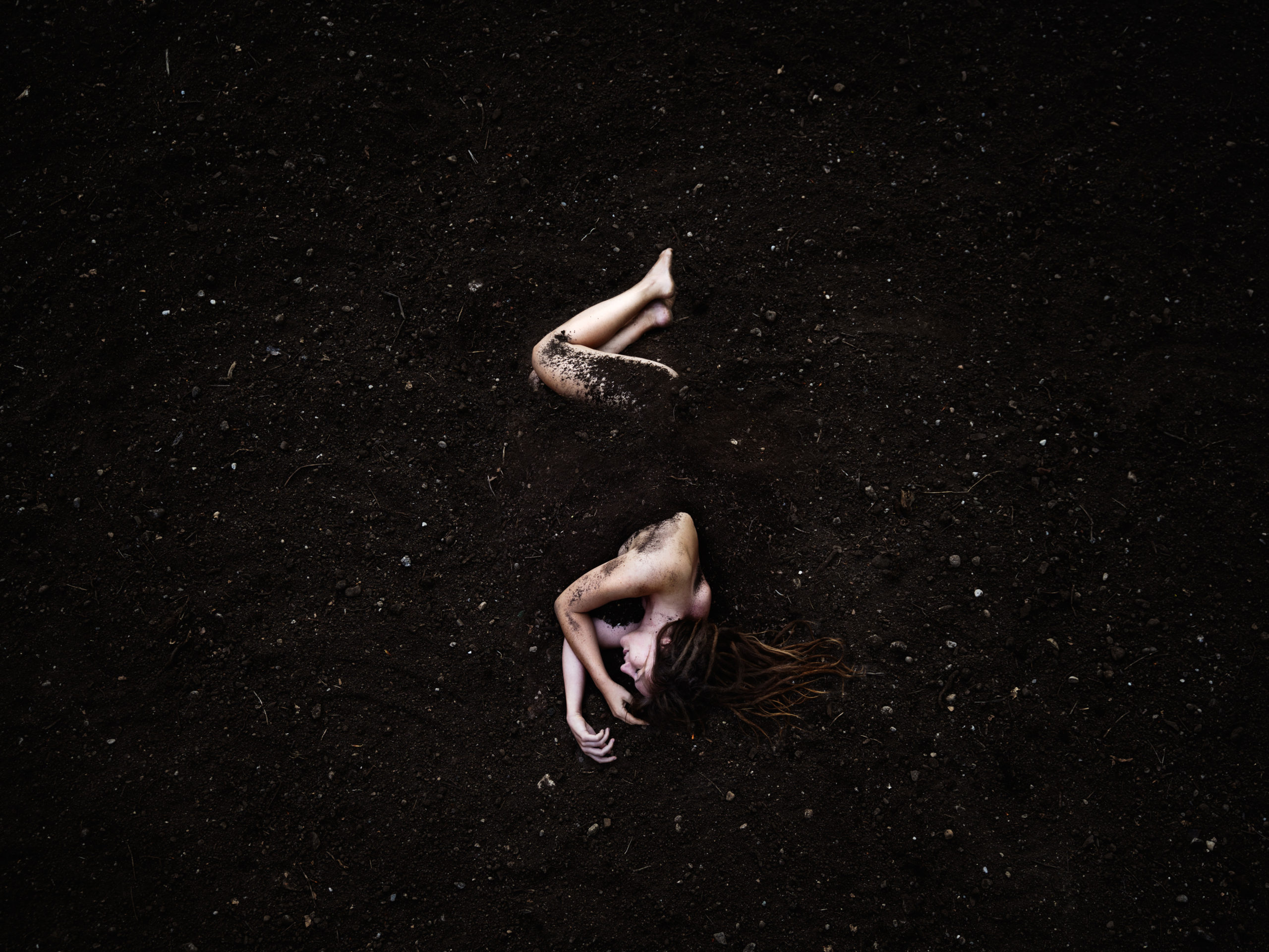 Mother earth self portrait photography, depicting a woman almost completely covered by soil, only her bare upper body and legs are visible among the dark surroundings.