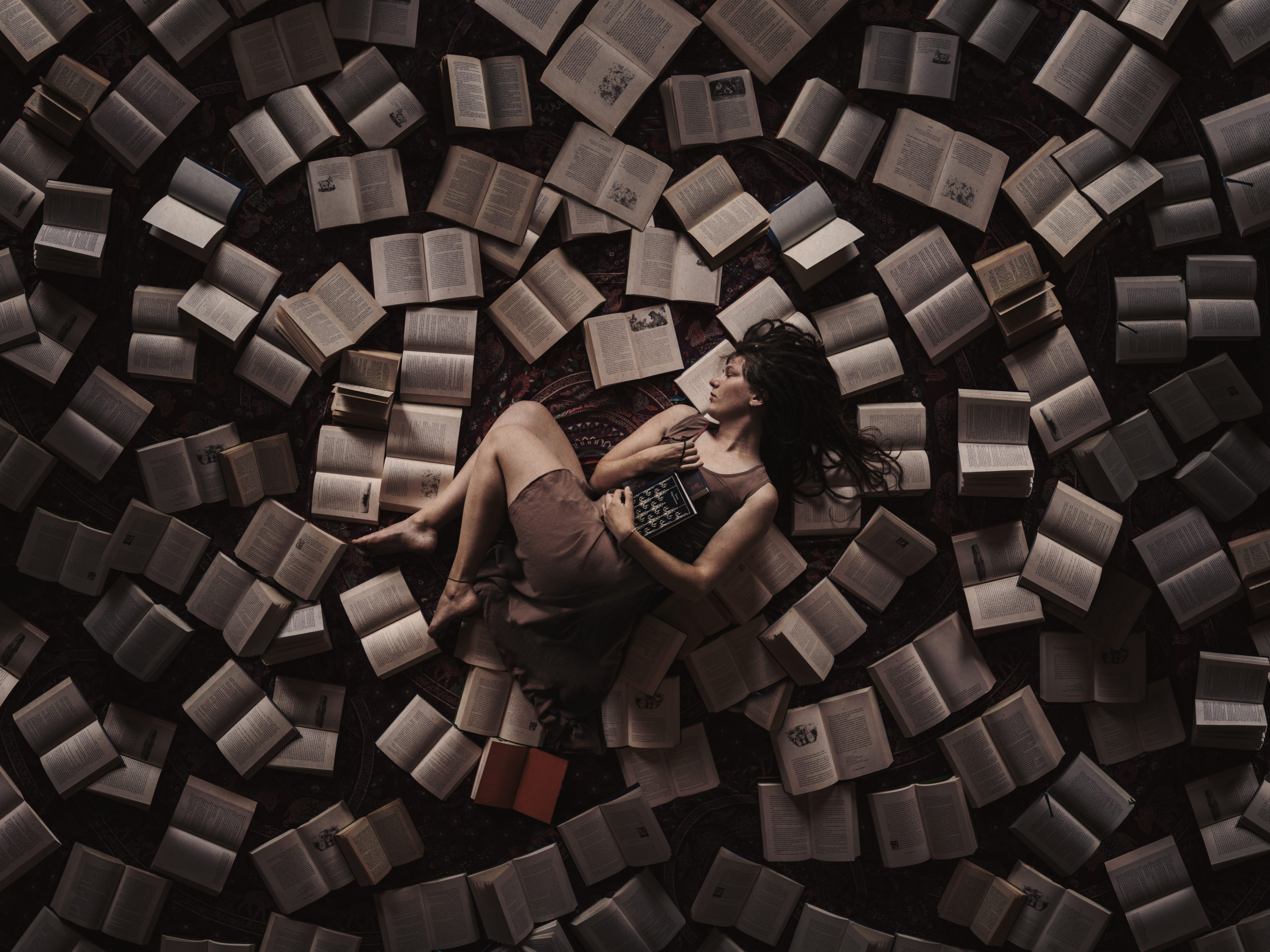 Self portrait photography by Anna Heimkreiter. The creative artwork shows a girl from above surrounded by books.