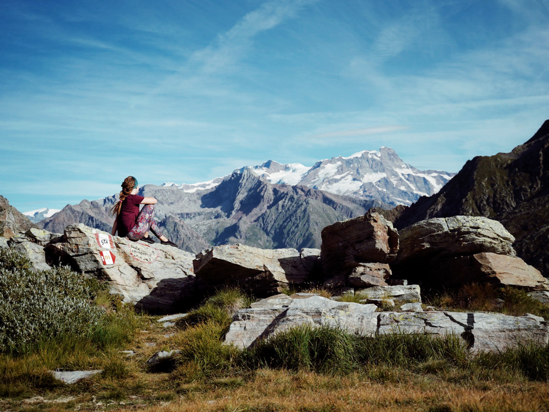 A female hiker enjoying the view onto snowy peaks.