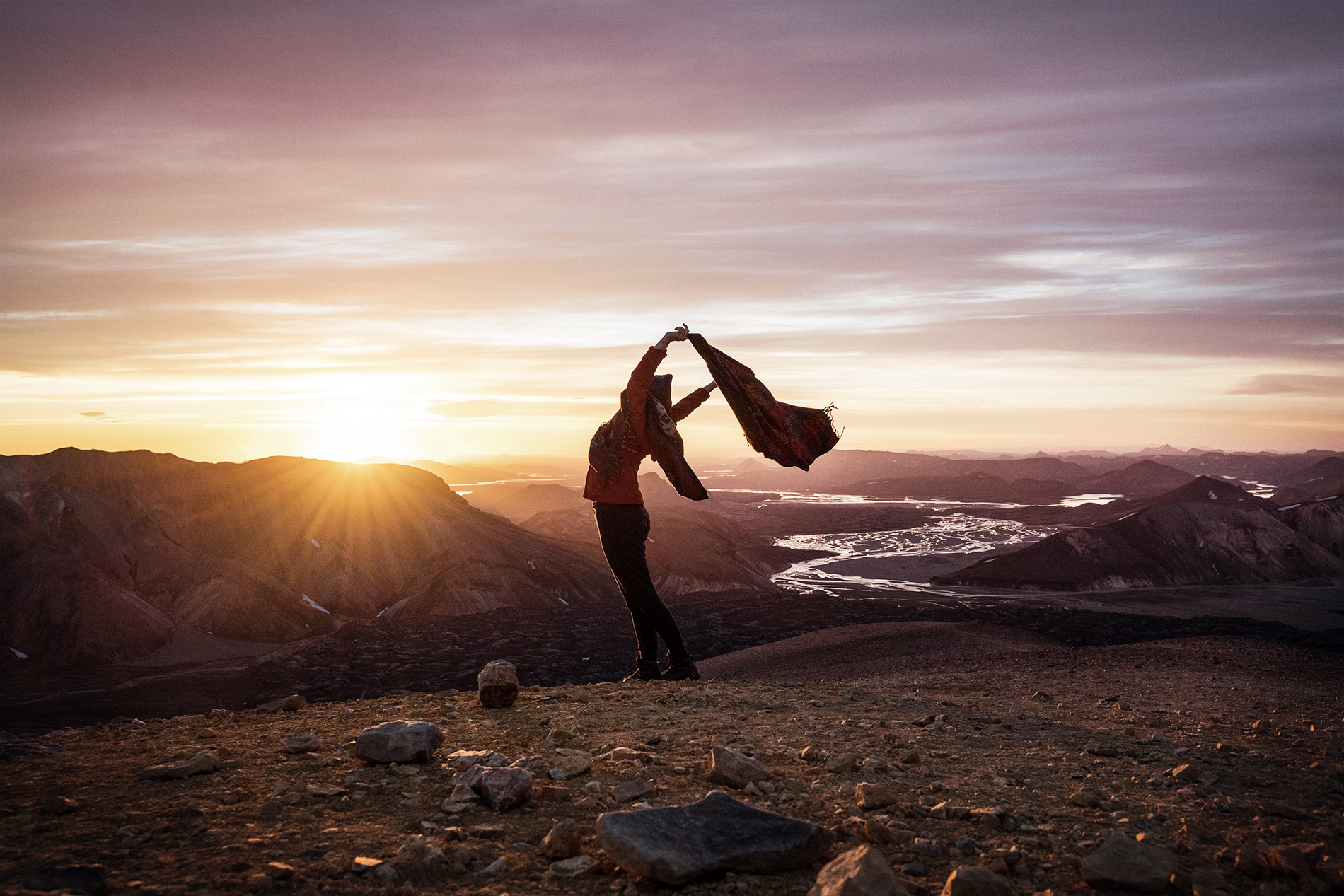 A hiker enjoying the feeling of freedom on top of a mountain at sunrise