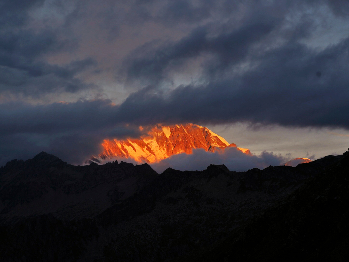 The monte rosa massiv as seen through the clouds at sunrise.