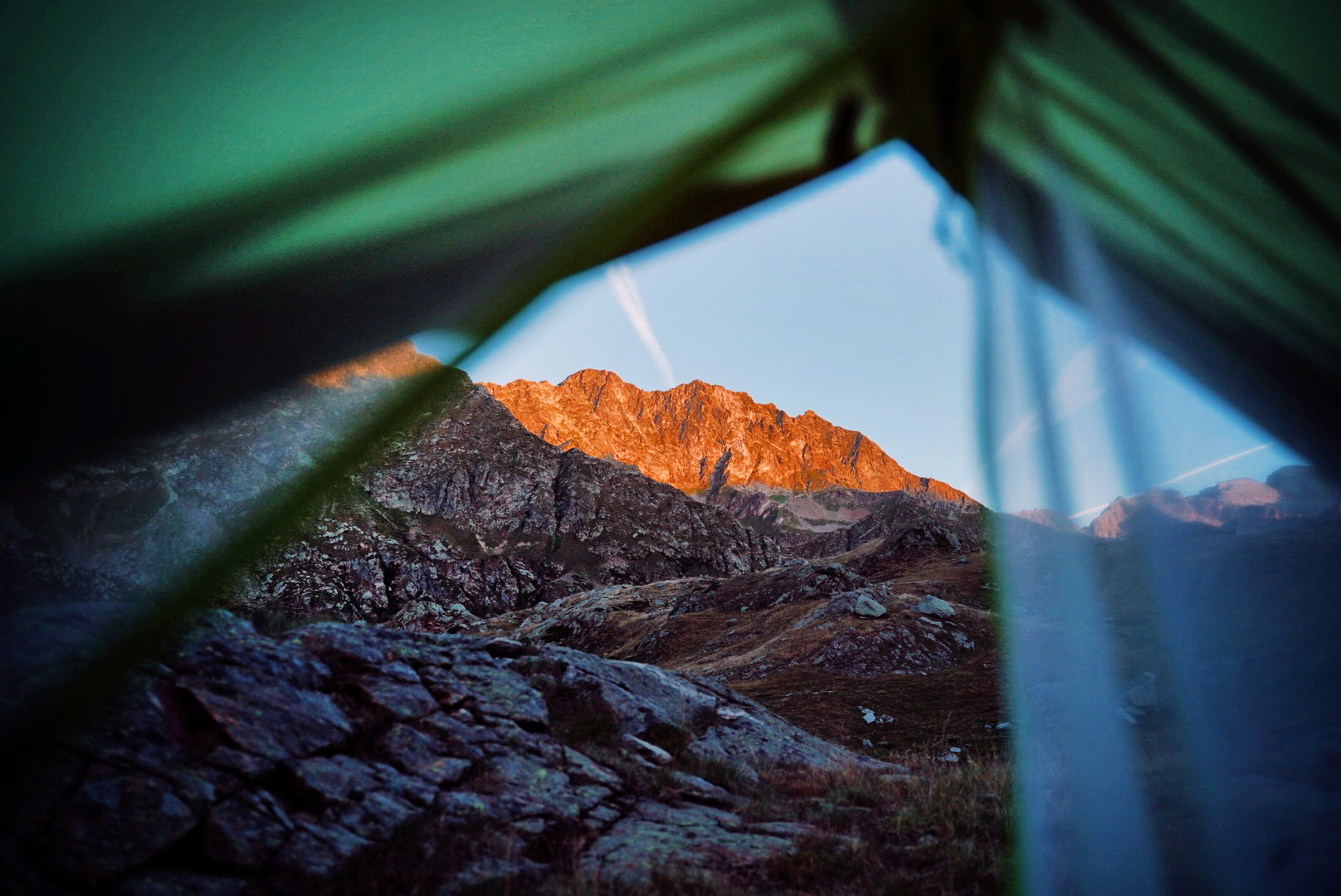 A beautiful sunrise in the mountains as seen from a tent.