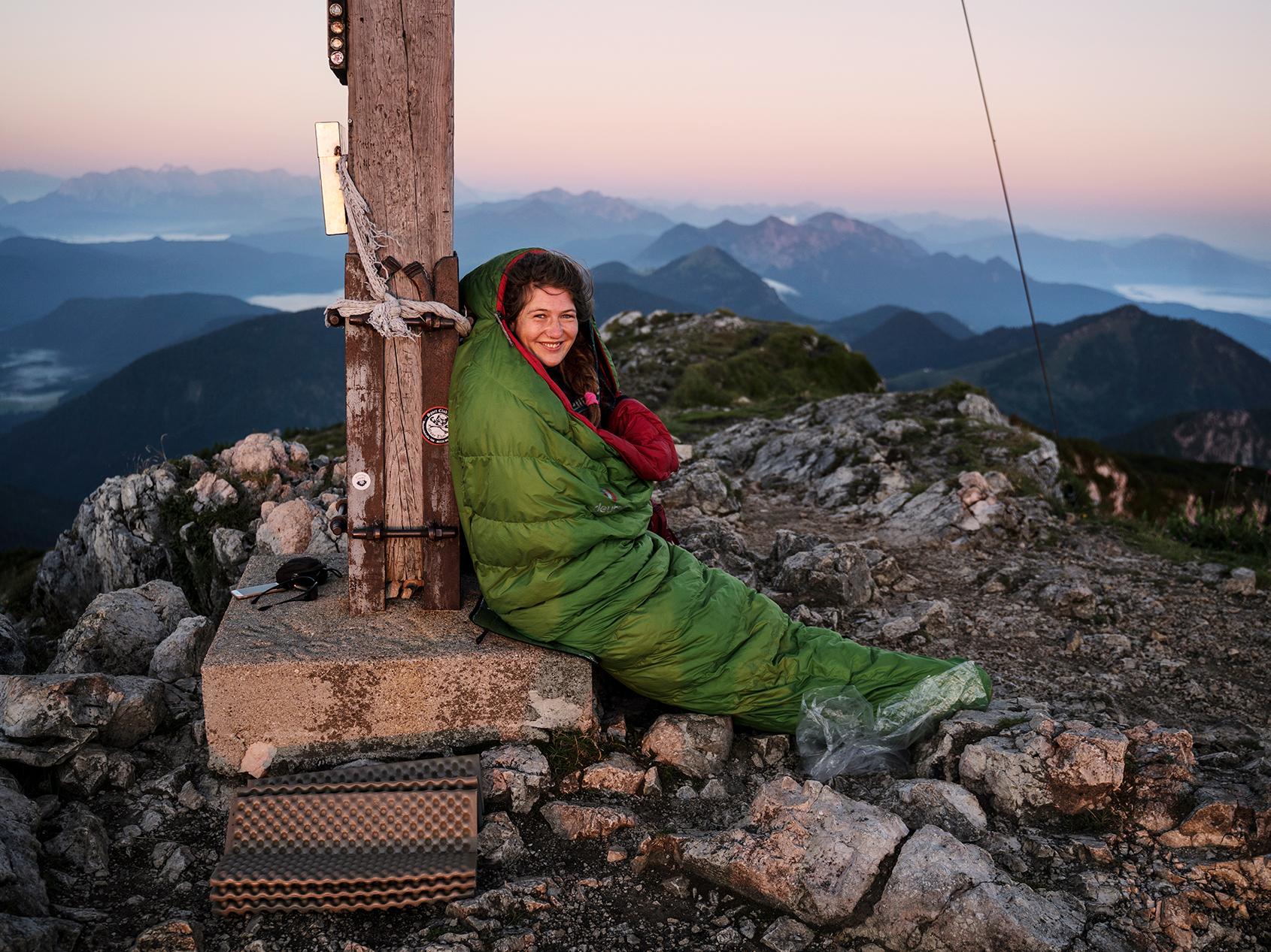 A hiker in her sleeping bag enjoying the peak views at sunrise.