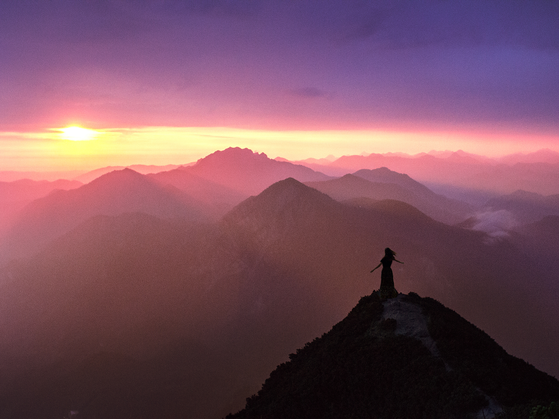 Layers of mountains at sunrise with a small person enjoying the freedom.