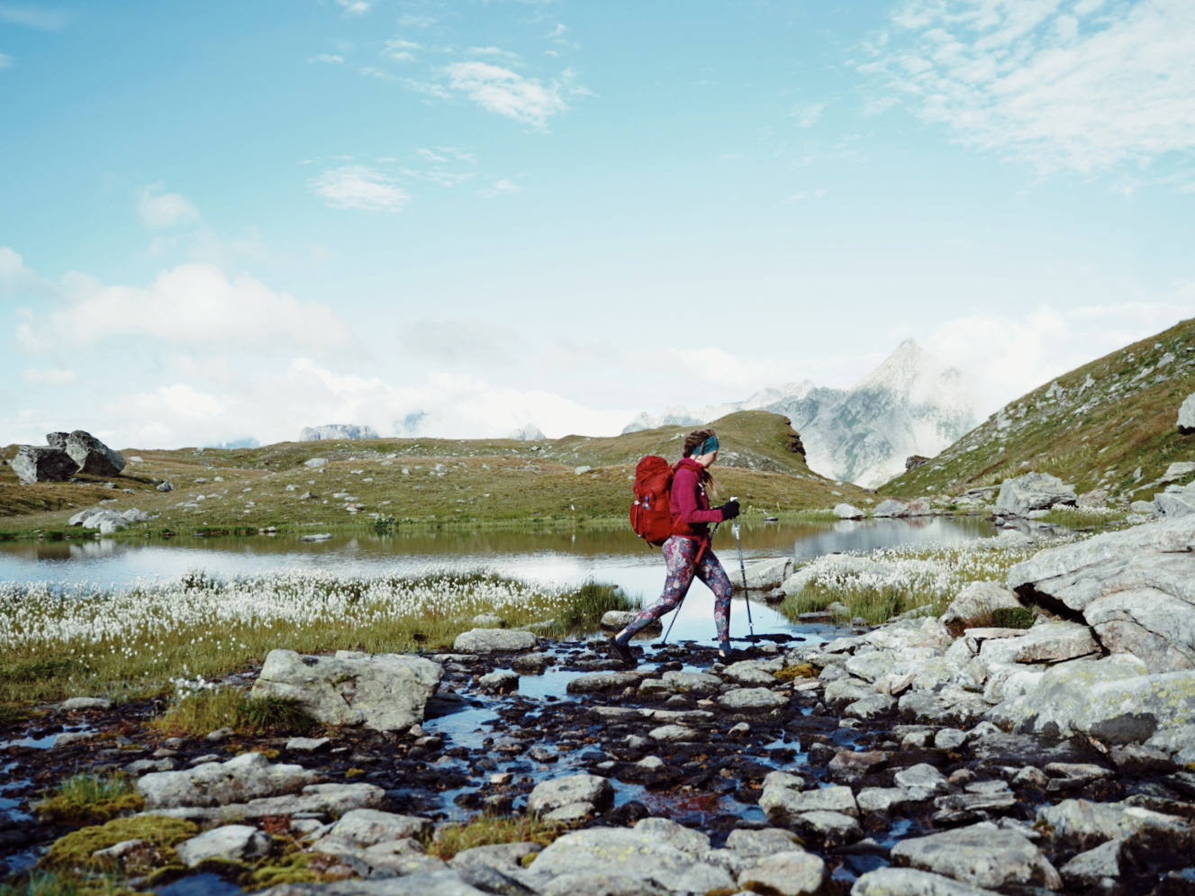A backpacker crossing a stream in the alps