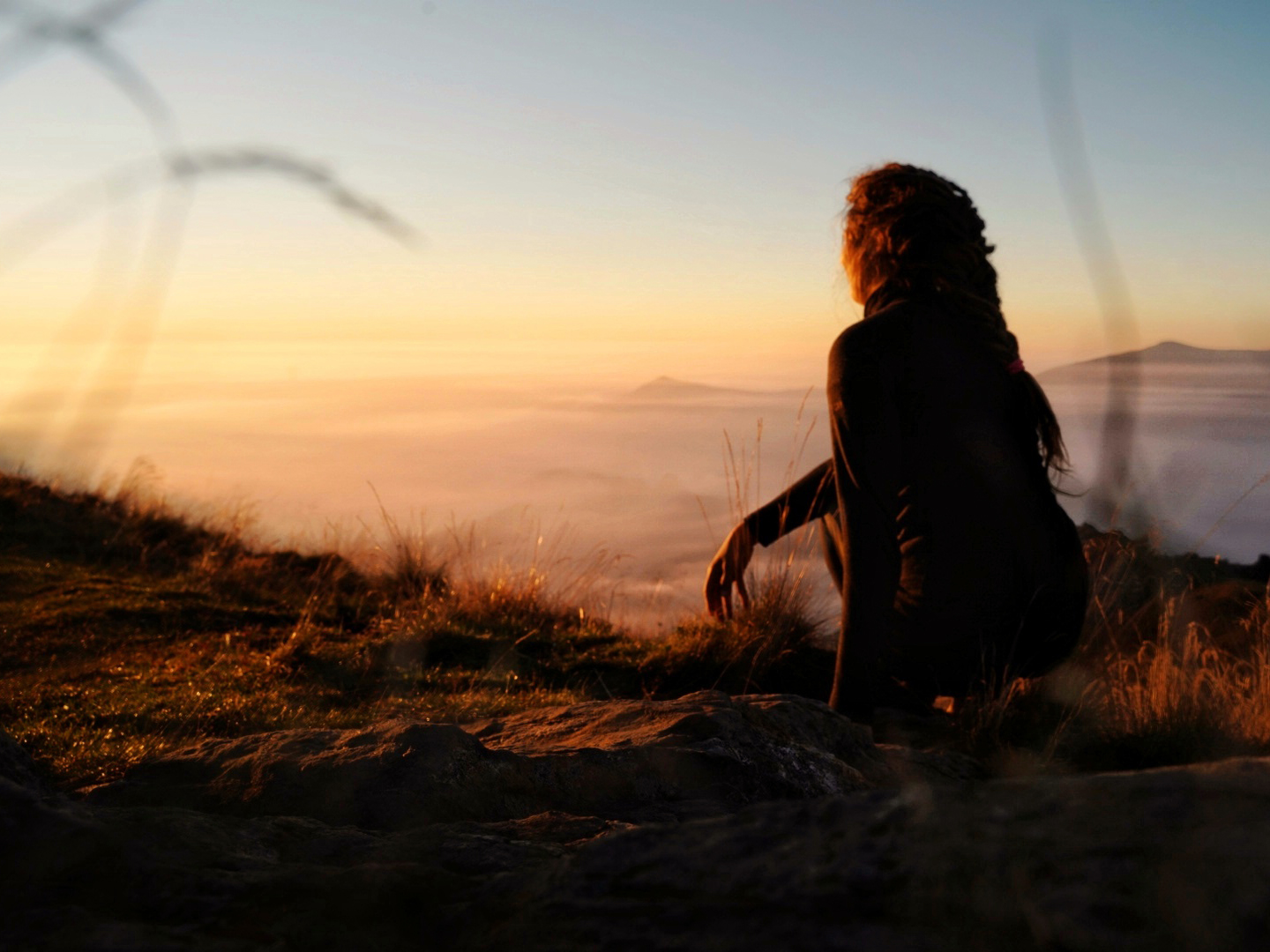 A woman watching the sun rise above the clouds.