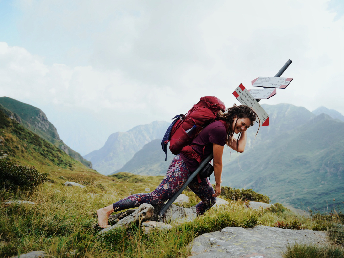 An exhausted, but happy hiker leaning onto a lopsided sign post.