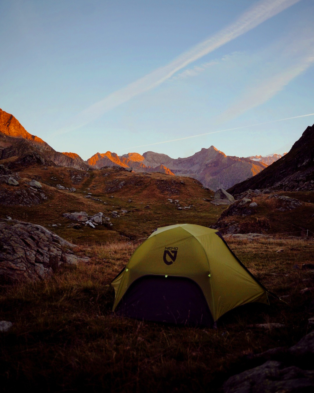 A tent at sunrise with a spectacular mountain view