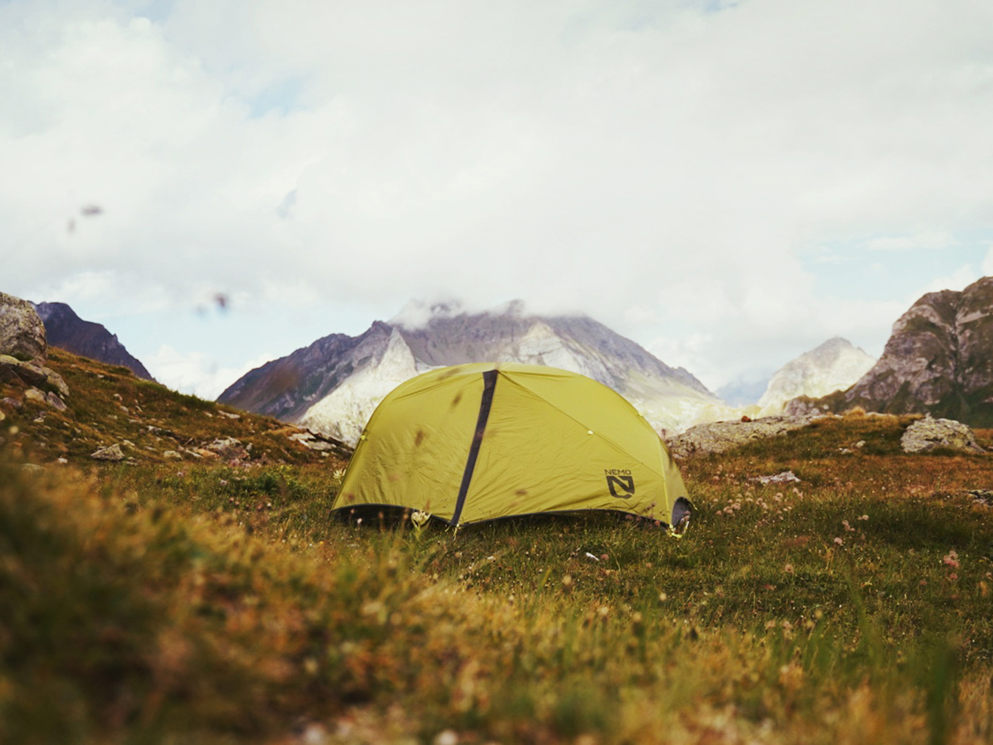 A green tent wild camping in the alps