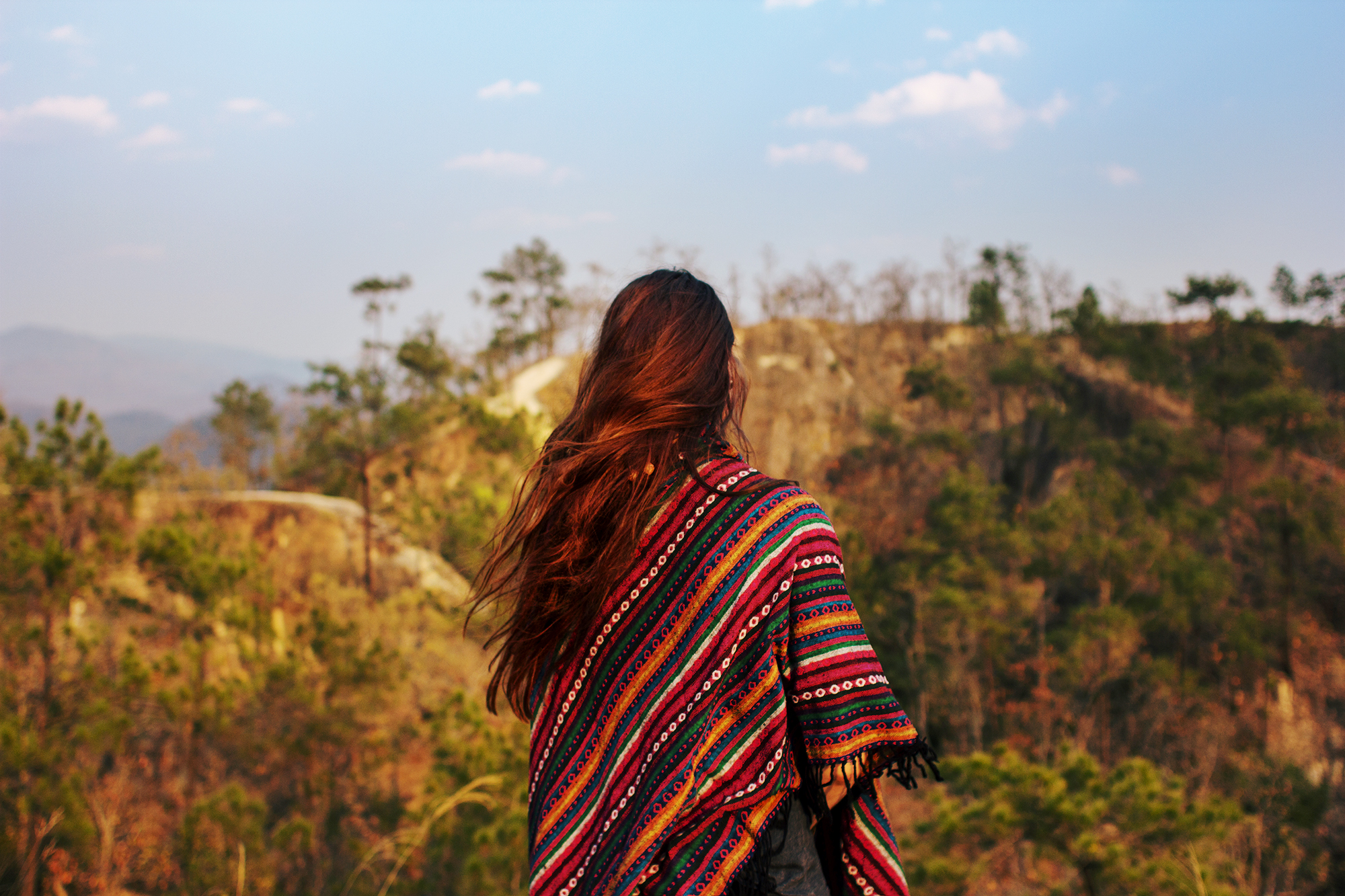 A young woman with long hair wearing a colorful poncho standing in a beautiful Thai landscape.