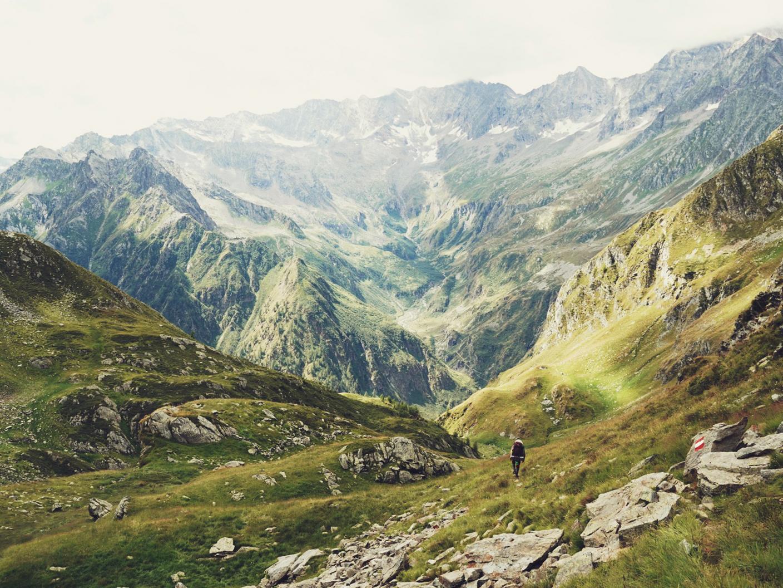 A hiker in the landscape of the Grande Traversata delle Alpi.