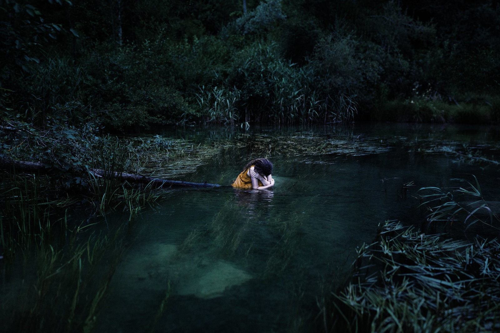 Fine art loneliness portrait depicting a girl in a sad pose in a lake.