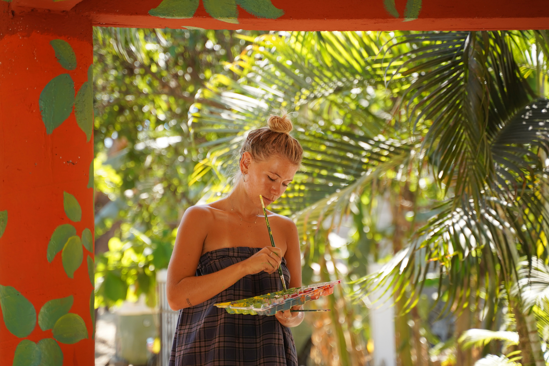 A young artist painting a mural in a tropical paradise.