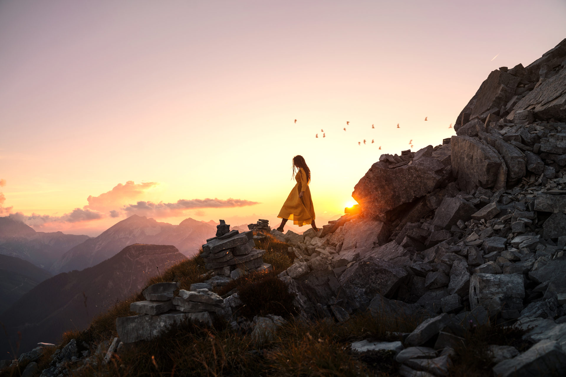 Self portrait photography by Anna Heimkreiter. The photo shows a woman wandering through the mountains at sunset. The mood is calm and peaceful.